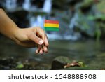 Small photo of Poor Bolivia in the hands of powerful people. Young man holds flag of Bolivia near stream. Concept of humanity and dominance. Prove of depraved and avariciousness. Problems with drogs.
