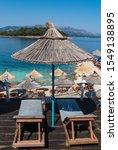 Small photo of Beach sunshade umbrella and sun bathing deck on beautiful blue sea of Southern Albania