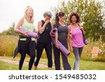 Small photo of Group Of Mature Female Friends On Outdoor Yoga Retreat Walking Along Path Through Campsite