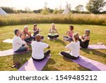 Small photo of Group Of Mature Men And Women In Class At Outdoor Yoga Retreat Sitting Circle Meditating