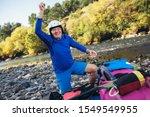 Senior man preparing for kayak tour on a mountain river. - stock photo