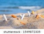 Cigarette Butts In Yellow Sand...