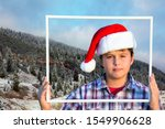 Small photo of Charming boy in a clownish cap of Santa Claus smiles through a white frame. The first snow. Magnificent panorama of Giau Pass, Dolomite Alps. Concept of Christmas and New Year tourism