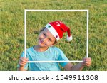 Small photo of Charming boy in a clownish cap of Santa Claus smiles through a white frame. Concept portrait and advertising photo. The background is green lawn