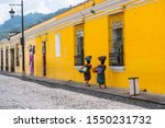 Two Mayan women are walking with their fruit baskets on a street in the city of Antigua in Guatemala.