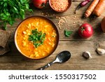 Red Lentil Soup with ingredients on wooden background, top view, copy space. Traditional turkish or arabic lentil and vegetable spicy soup, healthy vegan food.