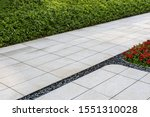 Small photo of Perspective View Monotone Gray Brick Stone Pavement on The Ground for Street Road. Sidewalk Driveway Pavers green grass