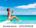 Small photo of Summer healthy eating woman drinking detox carrot juice for balanced diet weight loss bikini body lifestyle. Happy living girl enjoying sun tan holidays by the swimming pool of tropical hotel.