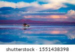 Car standing in middle of salt flat reflecting blue sky, Salar de Uyuni, Bolivia