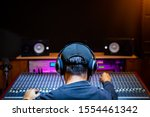 back of asian male professional music producer, sound engineer mixing a song on audio mixing console in recording studio. music production, post production concept - stock photo