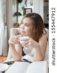 a woman holding her coffee cup... | Shutterstock . vector #155447912