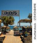 Small photo of Perissa, Greece - July 18 2019: The entrance to Dodo's Happy Zone beach bar and restaurant on Perissa Sea front