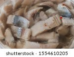 Stock photo  pieces of pickled herring in the package from the store on a wood background 1554610205