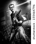 Musician plays a guitar on stage. Warning - stylized old photograph is present grain and high contrast. - stock photo