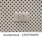 Small photo of The new white plug or the power plug in the white wall background with Circular Holes Cut in It.