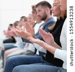 Small photo of group of young people sitting in a row applaud together