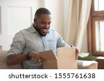 Small photo of Happy african american man sit on couch feel excited opening cardboard box delivery parcel, smiling biracial millennial male shopping online unpack unbox online order, overjoyed with service or goods
