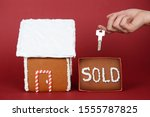Small photo of The hand-made eatable gingerbread house, hand with key on red background