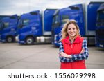 Small photo of Truck driver occupation. Portrait of woman truck driver in casual clothes standing in front of truck vehicles. Transportation service.
