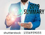 Small photo of Writing note showing 2019 Summary. Business photo showcasing brief comprehensive especially covering the main points of 2019 Male human wear formal suit presenting using smart device.