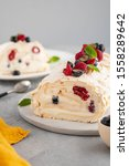 Small photo of Meringue roll cake with cream and raspberries. Roulade, summer dessert, closeup.