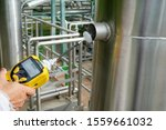 Small photo of Environmental officer use chemical detectors to monitoring volatile organic compounds (VOCs) that is released from the valve is part of the prevention of environmental impacts at in factory.