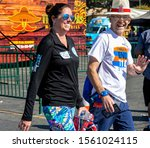 Small photo of Anaheim, CA / USA - Nov 3, 2019: Happy couple briskly walks across the finish line. The man is laughing and waving and the woman is grinning. Both are dressed casually and carrying water bottles.