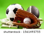 Small photo of Winning bet on sporting event, money in sport and sports betting conceptual idea with baseball glove, football, soccer ball and wad of cash isolated on green background