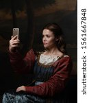 Small photo of Old and new, concept. Beautiful young Renaissance style woman taking selfie on phone. Beautiful mysterious girl in the style of a Renaissance painting.