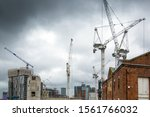 Small photo of Many construction cranes on the skyline against a dark moody sky. Used to develop and convert urban areas, Manchester, England, UK