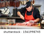 Small photo of Male butcher boning fresh ham in a modern butcher shop with metal safety mesh glove