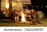 Friends warming up their hands during a cold night at camp fire. Retro camper van. Light bulbs in the background. - stock photo
