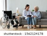 Small photo of Serious young female doctor comforting injured disabled handicapped senior lady patient tell diagnosis help old grandma with disability problem talk at medical checkup visit with wheelchair at home