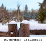 In the north of Finland near the town of Kemi is a Native American village. In the background a tent and a reindeer in the snow. In the foreground a wooden fence on which fresh snow lies.