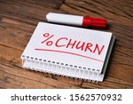 Small photo of Checkered Notepad With Churn Percent Text Near Red Marker Over Wooden Desk