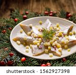 Stock photo christmas herrings fillets with apples pickled cucumbers red onion and spices on a ceramic plate 1562927398
