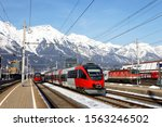 View of trains parking by the platforms of the Main Station in Innsbruck on a sunny winter day and snowy Nordkette mountain range of Karwendel Alps dominating the background under blue sky, in Austria