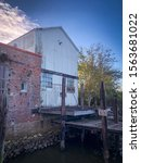 Photograph of the historic Apalachicola Marina in Apalachicola, FL.  A rustic, historic brick and metal  warehouse building on the water. Formerly an Ice Company in the 1920's.