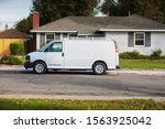 An unbranded home service van parked in front of a house for repairs or handyman work. - stock photo