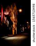 Small photo of Gritty Urban alley way with hotel sign lit in neon - Noir look,