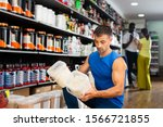 Small photo of Portrait of interested athletic man choosing food supplements in large assortment of sport nutrition shop