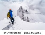 Small photo of An alpinist climbing an alpine ridge in winter extreme conditions. Adventure ascent of alpine peak in snow and on rocks. Climber ascent to the summit. Winter ice and snow climbing in mountains.