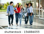 Stock photo full length of cheerful university students walking on campus 156886055