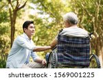 Small photo of asian son talking to and comforting wheelchair bound father