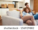 couple relaxing on sofa with... | Shutterstock . vector #156929882