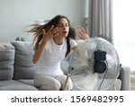 Small photo of In living room without air-conditioner tired from summer heat young woman turned on floor ventilator waving her hands to cool herself, female sitting on couch suffers from unbearable too hot weather