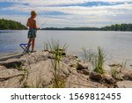 boy fishing on the lake in... | Shutterstock . vector #1569812455