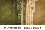 Small photo of Aerial view of a combine that unloads grain from its grain compartment into a truck van. One truck drove off and the next truck drove up to receive wheat grains. View from the top to a sloping yellow
