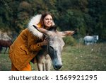 A woman in a warm jacket hugs...