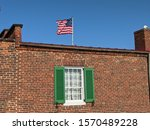 Federal style brick barracks with the Star Spangled Banner flying above it. Fort McHenry, Baltimore, Maryland, USA